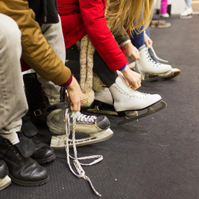 Teenagers putting on ice skates